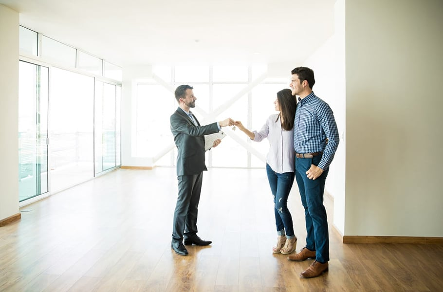 Couple Getting Keys From Realtor Of Their New Home