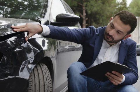 Inspecting Car Damage After A Crash
