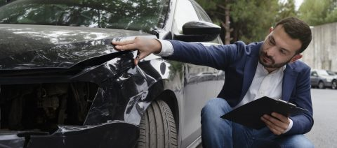 auto insurance adjuster looking at car accident