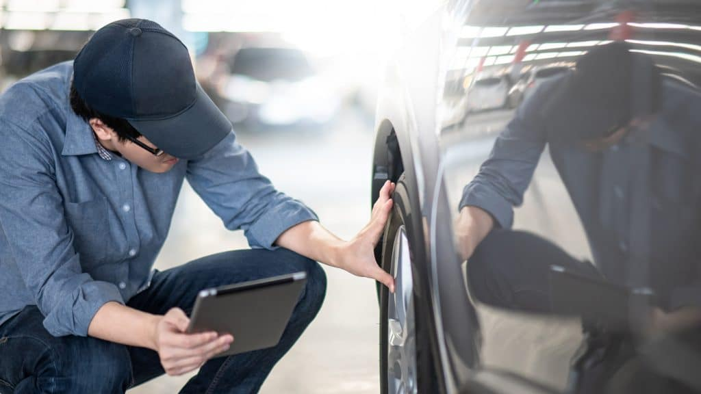 insurance claim adjuster inspecting a car after an accident