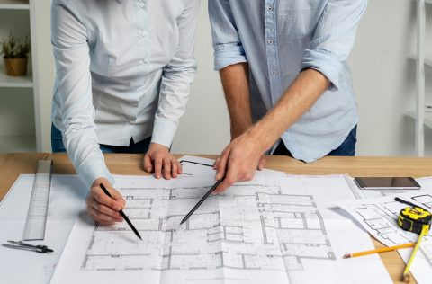 Cropped two builder person specialist designer in formalwear shirt stand on workstation with divider pencil ruler measurement on table discuss analyzing expertise inspect scheme make paper paperwork
