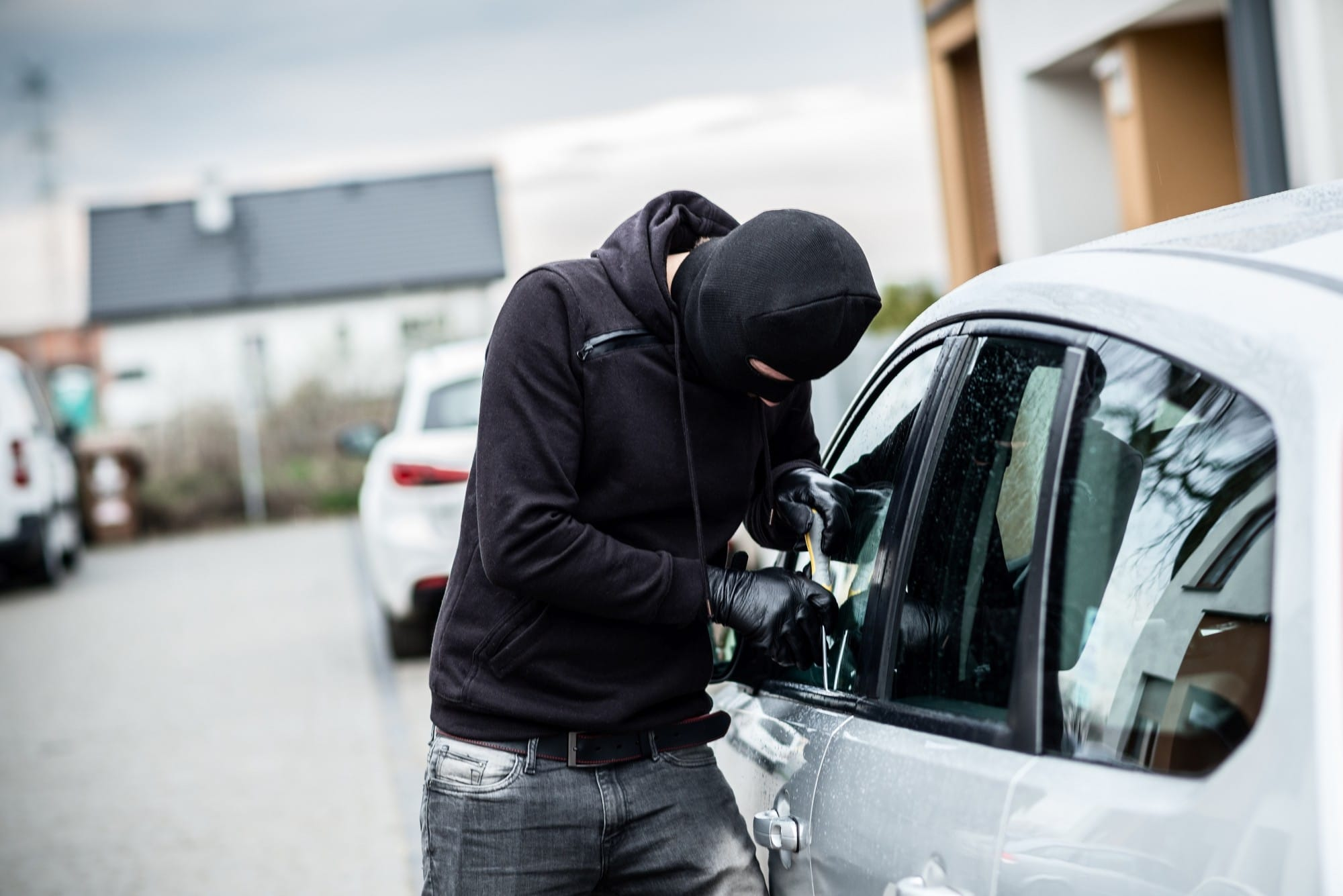 Car thief trying to break into a car with a screwdriver. Car thief, car theft.