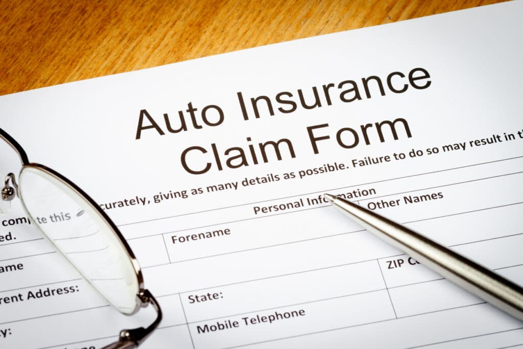Filing for third-party claim concept, an auto insurance claim form about to be filled out.