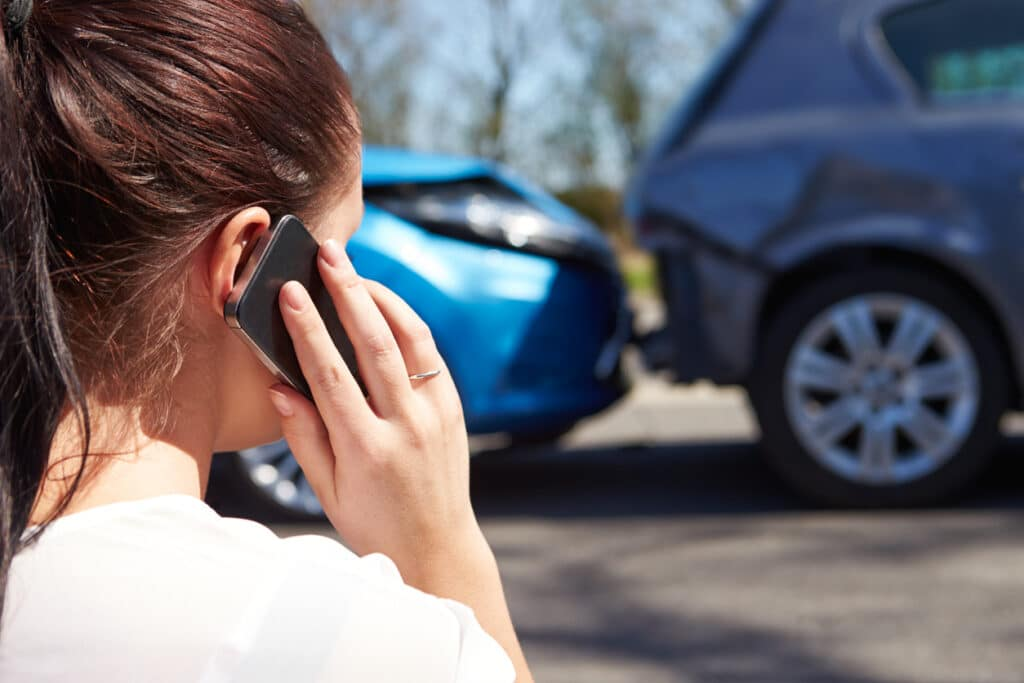 Woman calling using a mobile phone and reporting about a car accident.