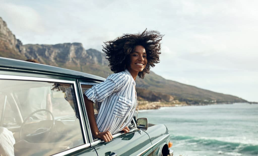 A woman smiling near the ocean on her road trip.