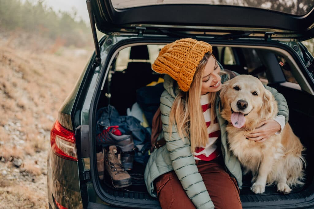 A woman petting her dog in the back of a car as they take a break from their road trip.